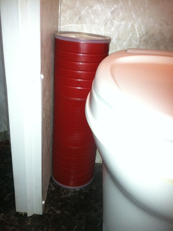 Small Bathroom Storage Ideas - coffee cans taped together hold toilet paper behind or beside the toilet.