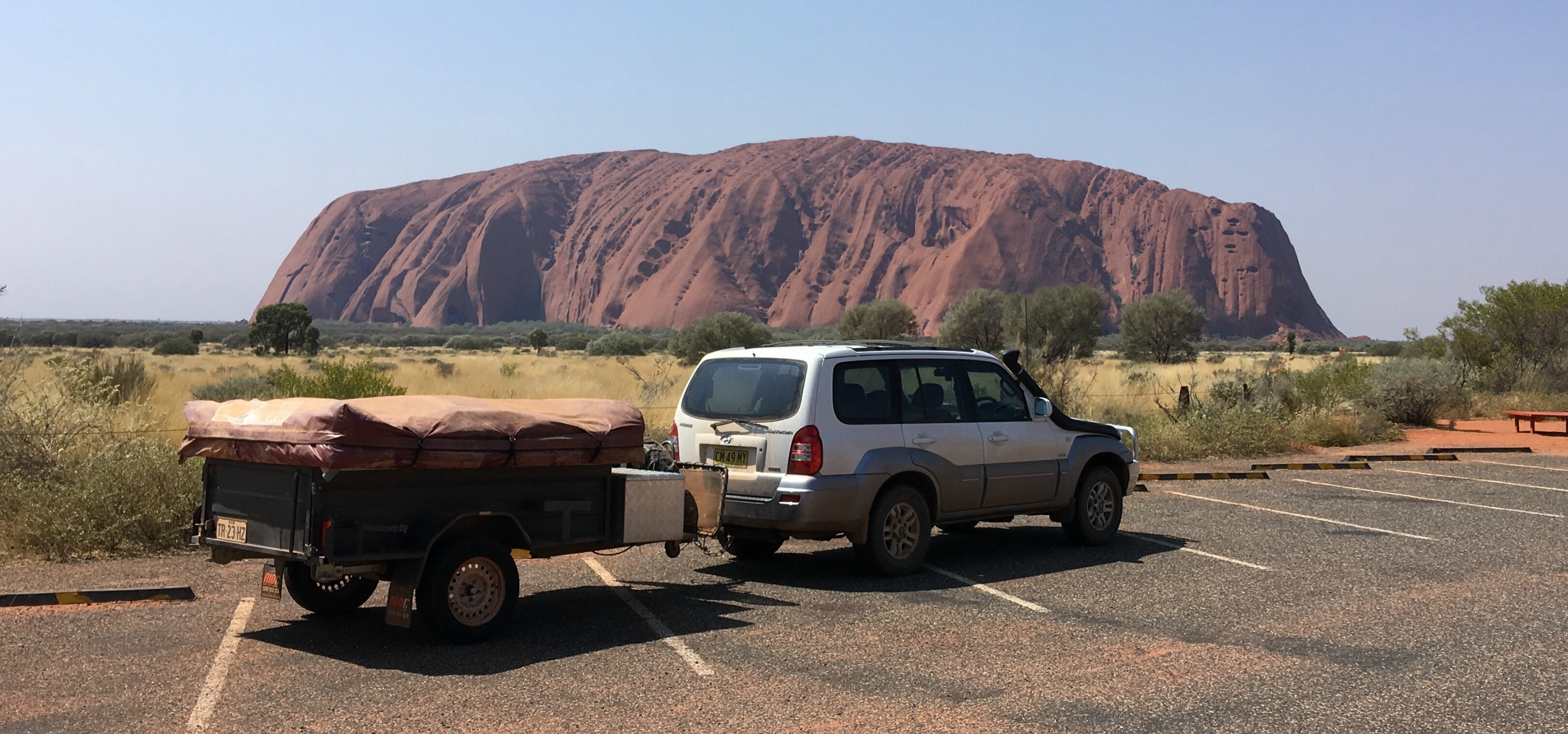 How to earn money while rving - our road trip around Australia - car and camper trailer at Uluru, Northern Territory, Australia