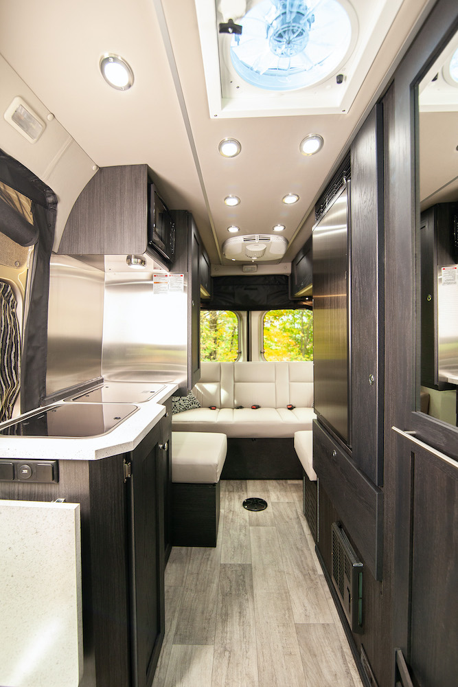 White upholstery and dark wood cabinets inside a modern camper van