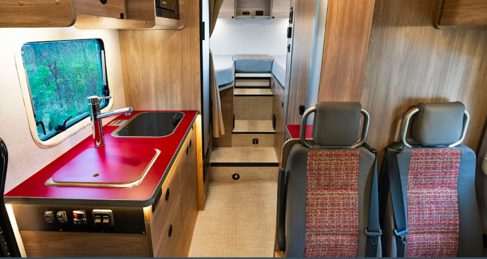 Wooden interior of small RV with a rich red kitchen countertop