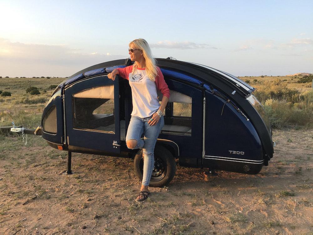 Woman standing beside a small teardrop camper