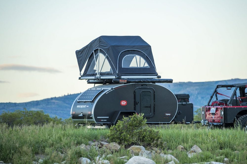 Small teardrop camper with roof top tent set up in a remote area