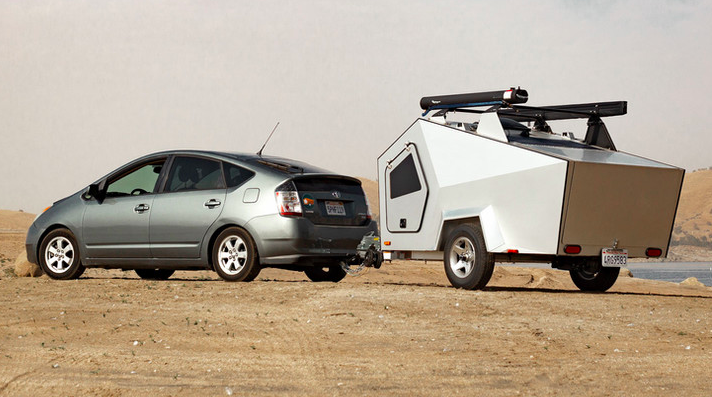 Geometric shaped teardrop camper hitched to a Prius