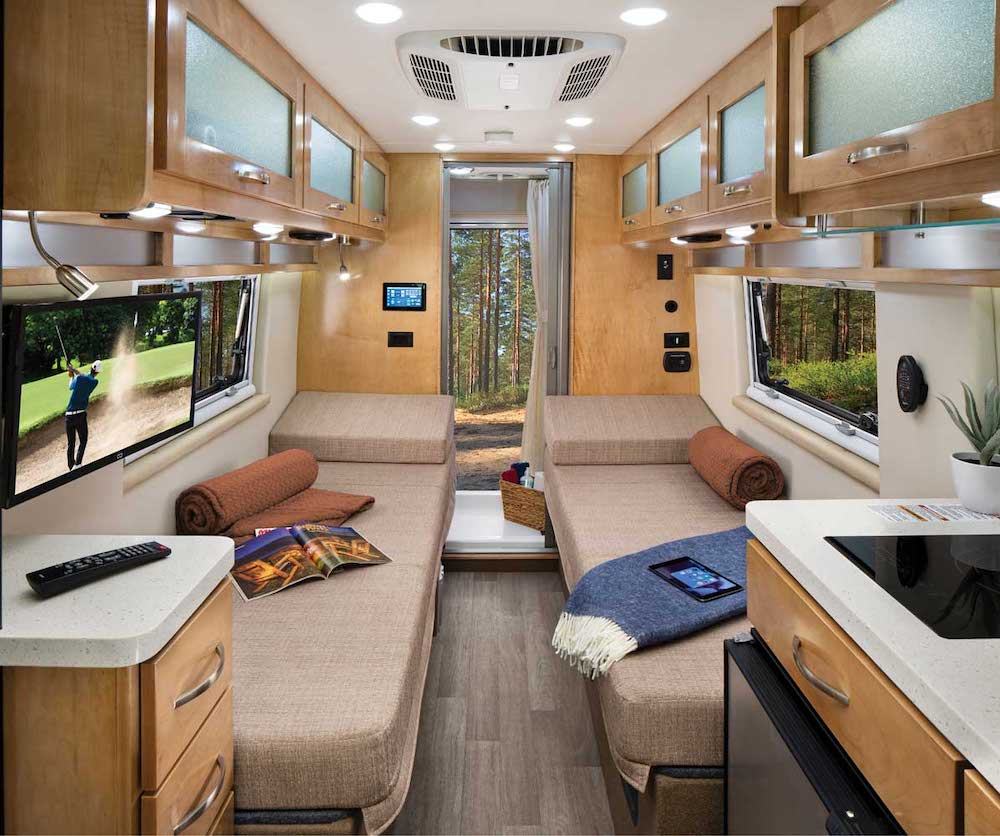 Interior of a beige/brown camper van, looking towards the rear doors, showing a bench seat on each side.