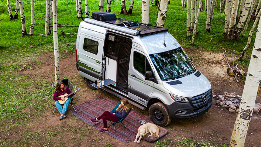 Aerial view of the Winnebago Revel camper van with two women sitting out the front on camping chairs, and a dog.