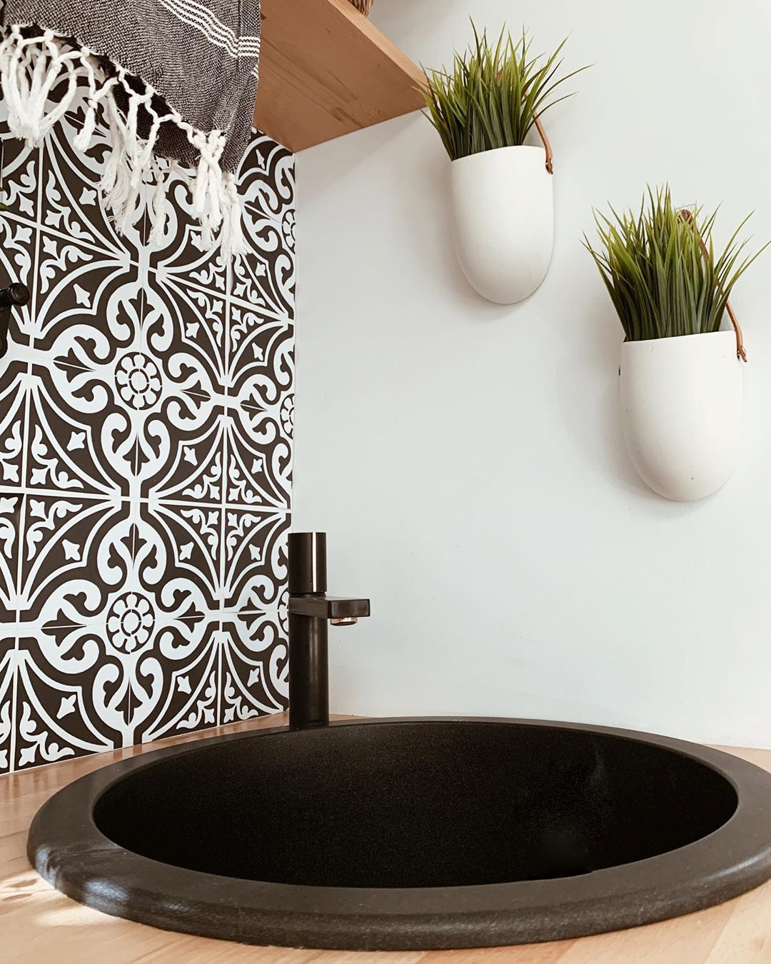 Black and white splashback behind a black RV sink and tap