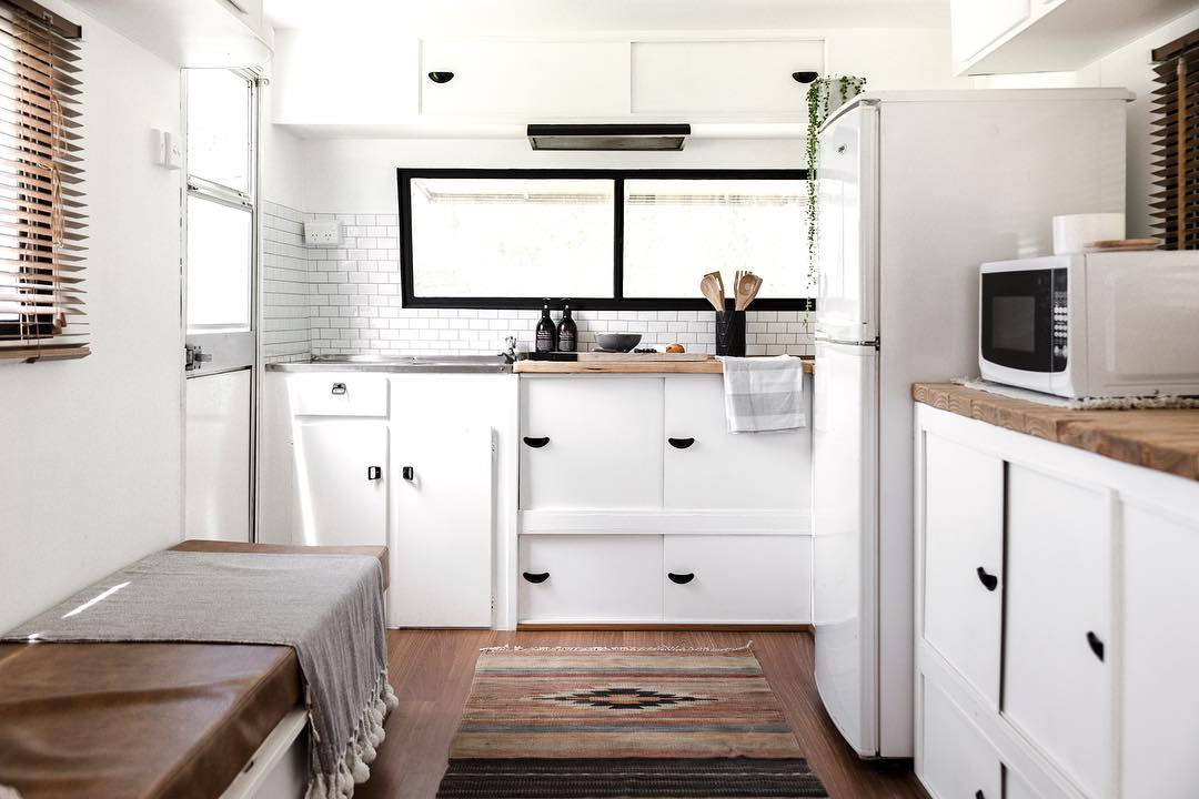 Interior of renovated travel trailer showing a white kitchen at one end of the carvavan