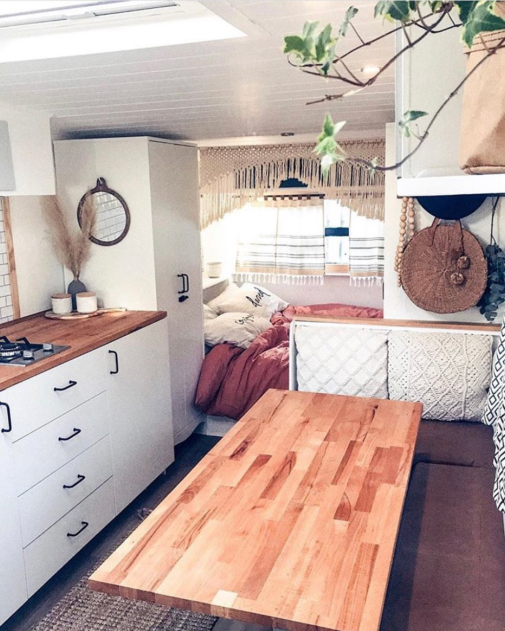 Interior of a renovated travel trailer showing the dining area and kitchen