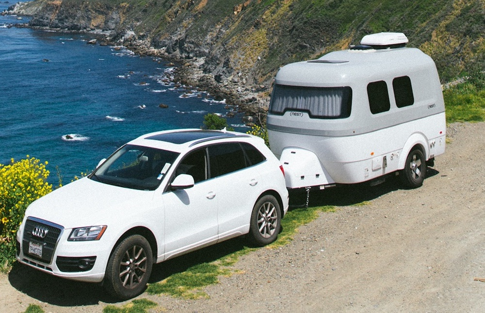 White car and fiberglass caravan parked at a coastal view