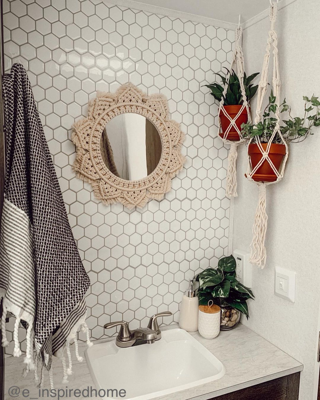 Small round mirror with macrame frame and hanging plants in a small camper bathroom