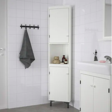 White cabinet in the corner of a white bathroom