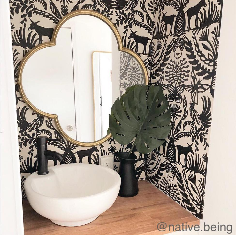 Decorative mirror hanging on a black and white wallpapered wall over a small bathroom sink