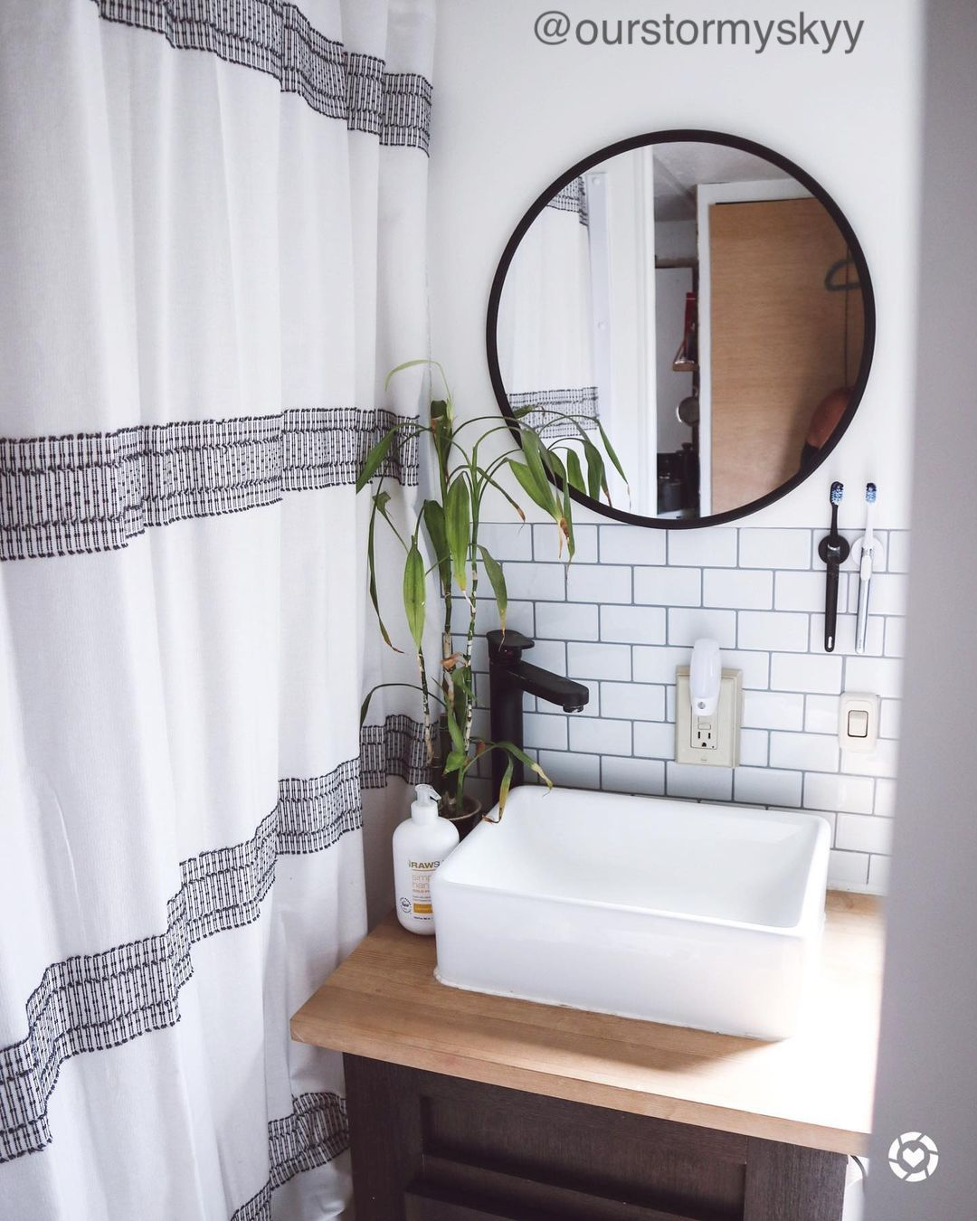 Small bathroom with vanity, wall mirror and shower curtain