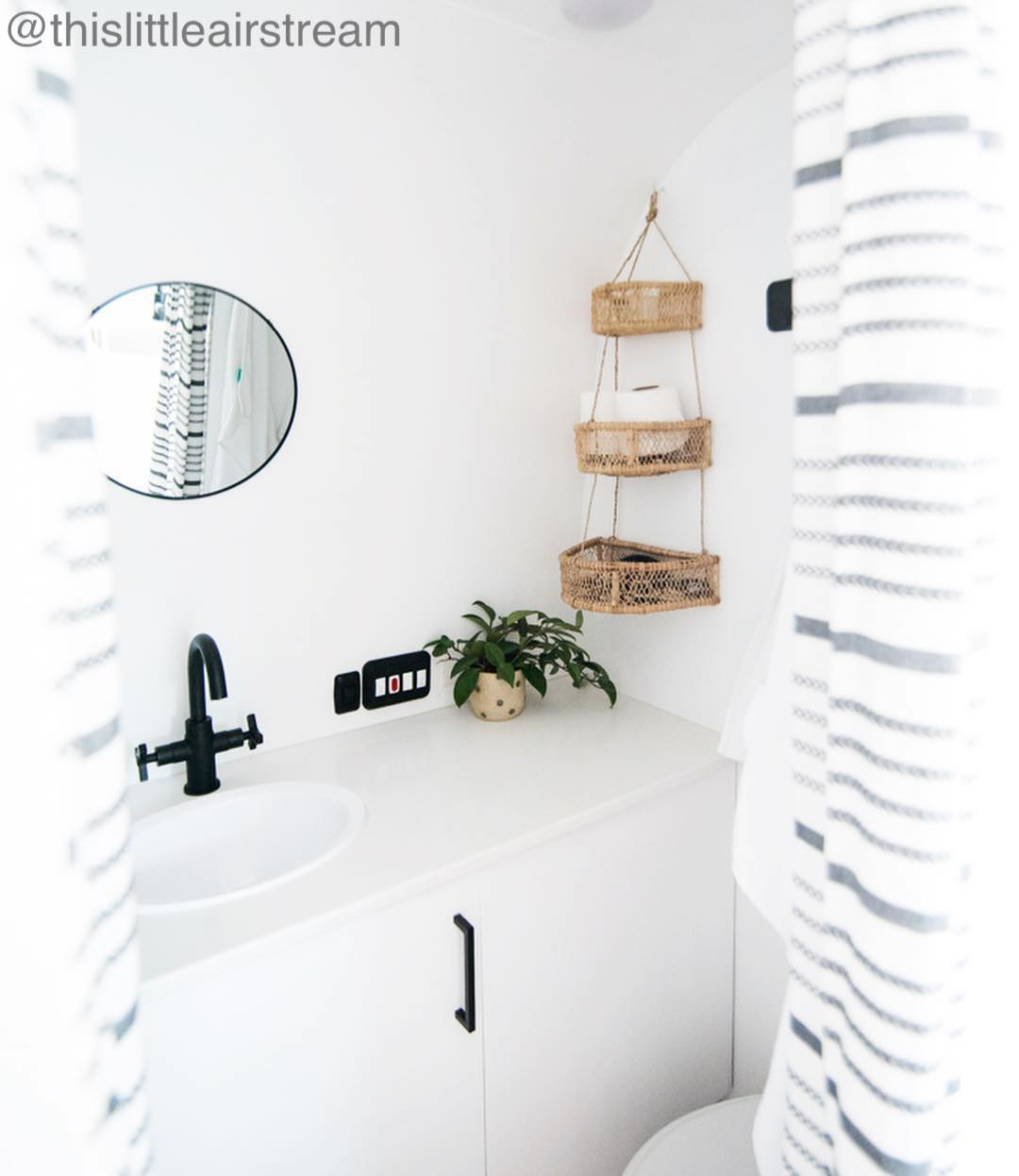 White small bathroom with hanging baskets