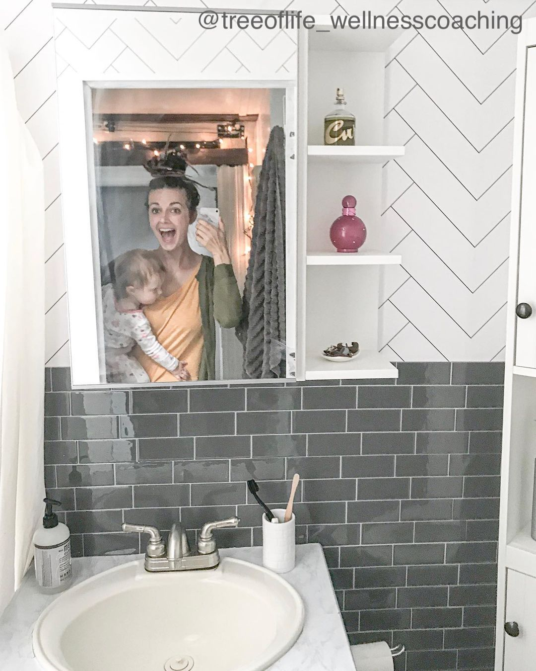 Smiling woman seen holding a baby in the reflection of a small bathrooms mirror