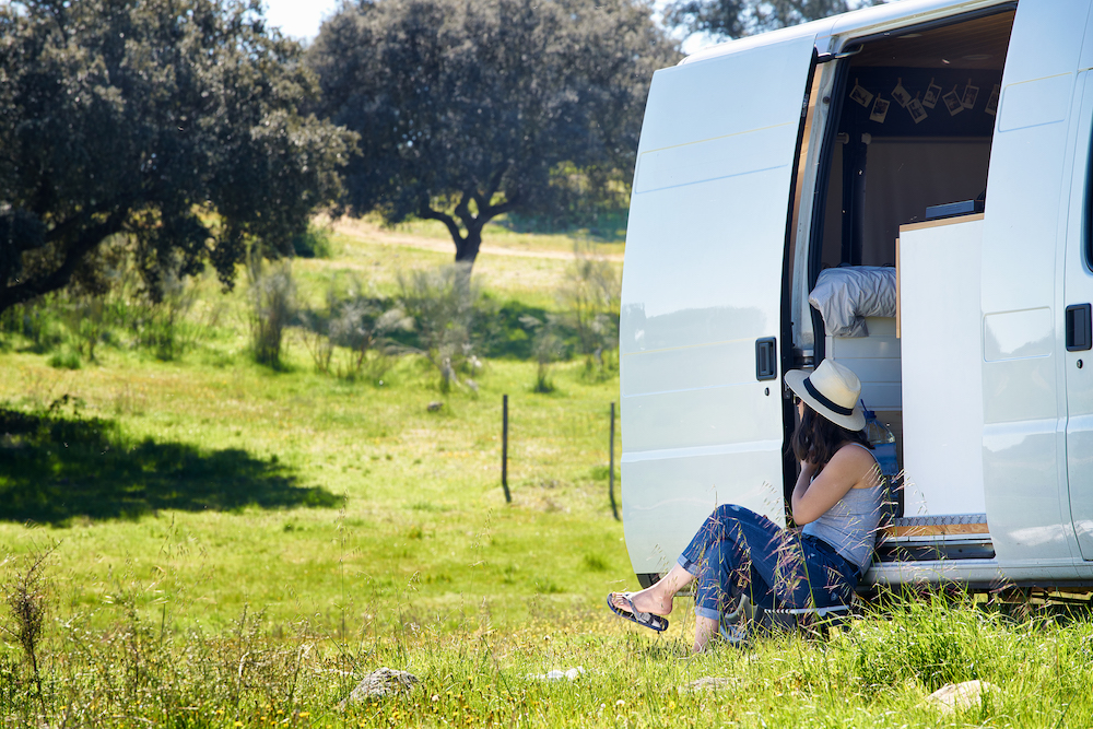 Woman sitting on a campervan step gazing at the rolling green hills.