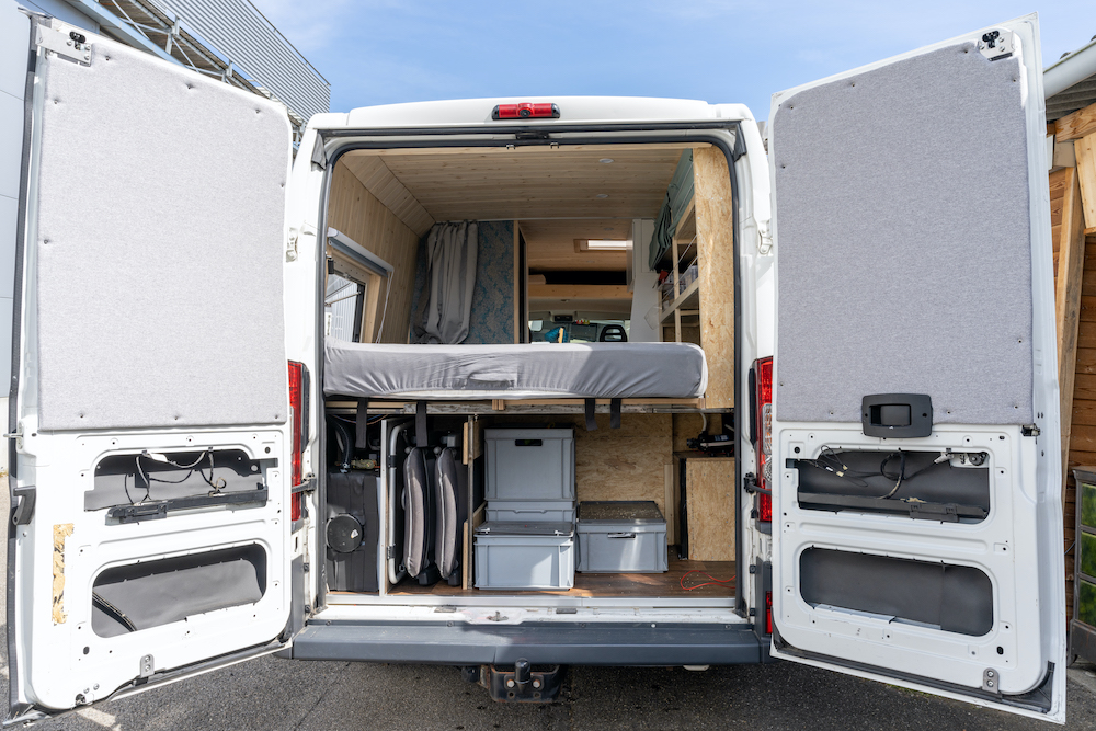 Organization system in the back of a camper van with the door open.