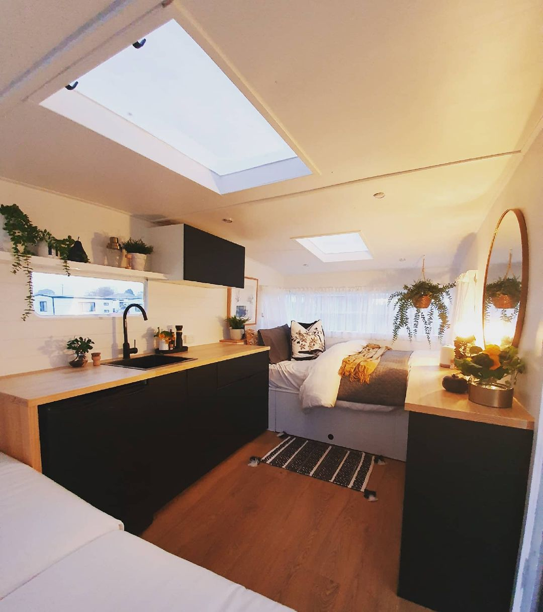 Interior view of a remodeled travel trailer showing the bed and kitchen area.